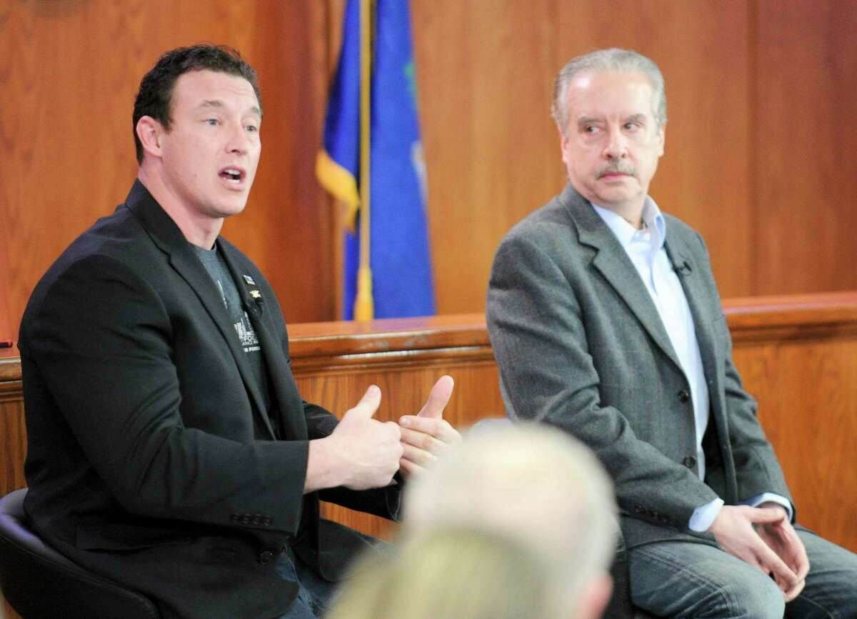Tom Borelli, at right, one of three panelists listens as Greenwich resident Carl Higbie, a former employee of the Trump administration, addresses a question raised by town resident David Cox, of Old Greenwich, during the broadcast of America's Voice at the Greenwich Town Hall on Jan. 30 in Greenwich.