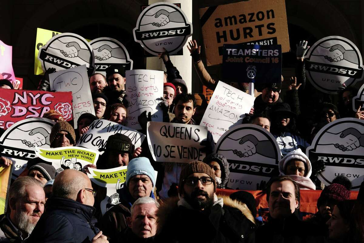 Demonstrators hold signs during a protest against Amazon outside of City Hall in the Long Island City neighborhood in the Queens borough of New York, U.S., on Wednesday, Jan. 30, 2019. Photographer: Sangsuk Sylvia Kang/Bloomberg