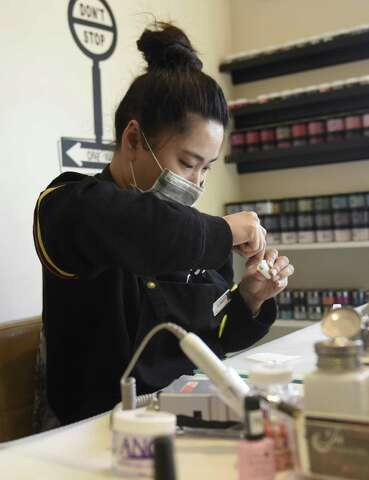 <p>Employees work at a nail salon in Stamford, Conn. Wednesday,