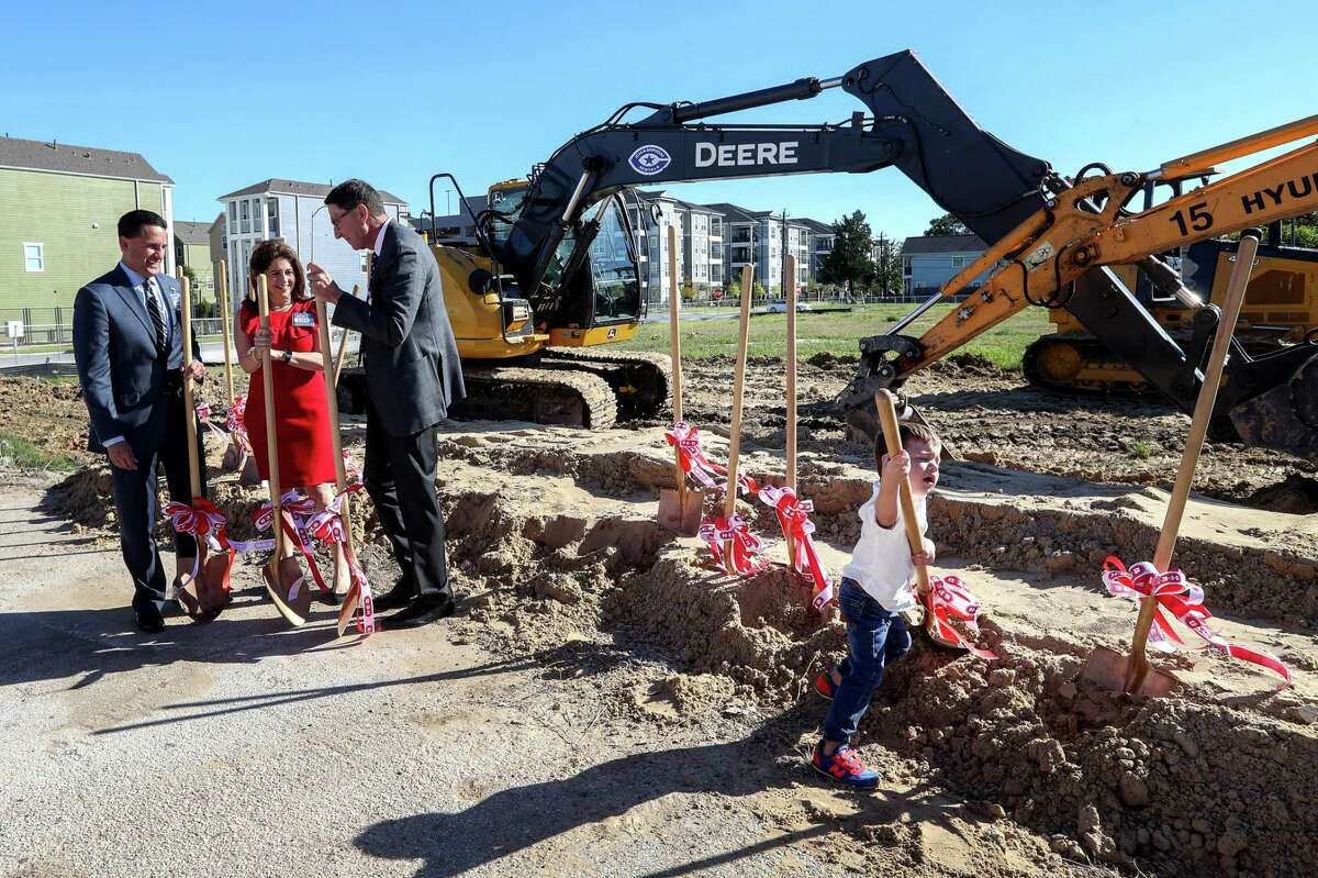 Stig Peterson, from right, grandson of Scott McClelland, HEB president of food and drug, plays with a shovel while his grandfather talks to Lisa Helfman, HEB director of real estate, and Armando Perez, senior vice president of HEB Houston, during a groundbreaking ceremony for a new HEB location in the Heights neighborhood, Tuesday, Oct. 24, 2017, in Houston. Last November, Heights residents voted to repeal an alcohol ban, making it possible for HEB to build the store. ( Jon Shapley )