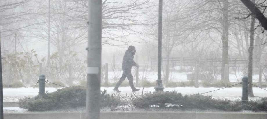 A pedestrian braves the bitter cold on Washington Boulevard during a winter snow squall on Wednesday in Stamford. Photo: Matthew Brown / Hearst Connecticut Media / Stamford Advocate