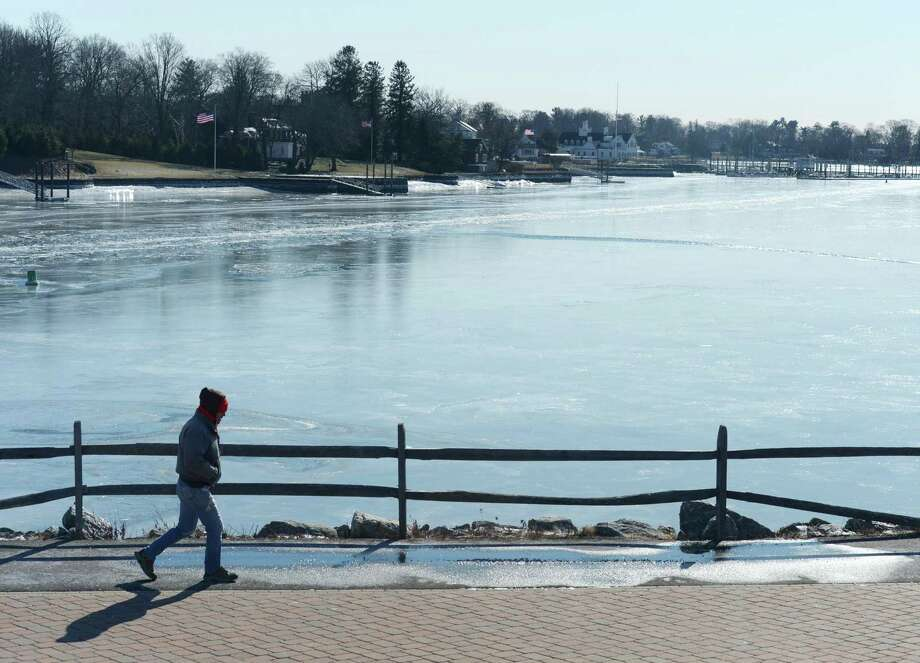 Cos Cob's Tony Marrone goes for a walk in the cold weather as Cos Cob Harbor is frozen behind him at Cos Cob Park in the Cos Cob section of Greenwich, Conn. Thursday, Jan. 31, 2019. The area saw single-digit temperatures with wind chills below zero on Thursday. The town opened several warming centers around the community and Greenwich public schools opened two hours later because of the cold. Photo: Tyler Sizemore / Hearst Connecticut Media / Greenwich Time