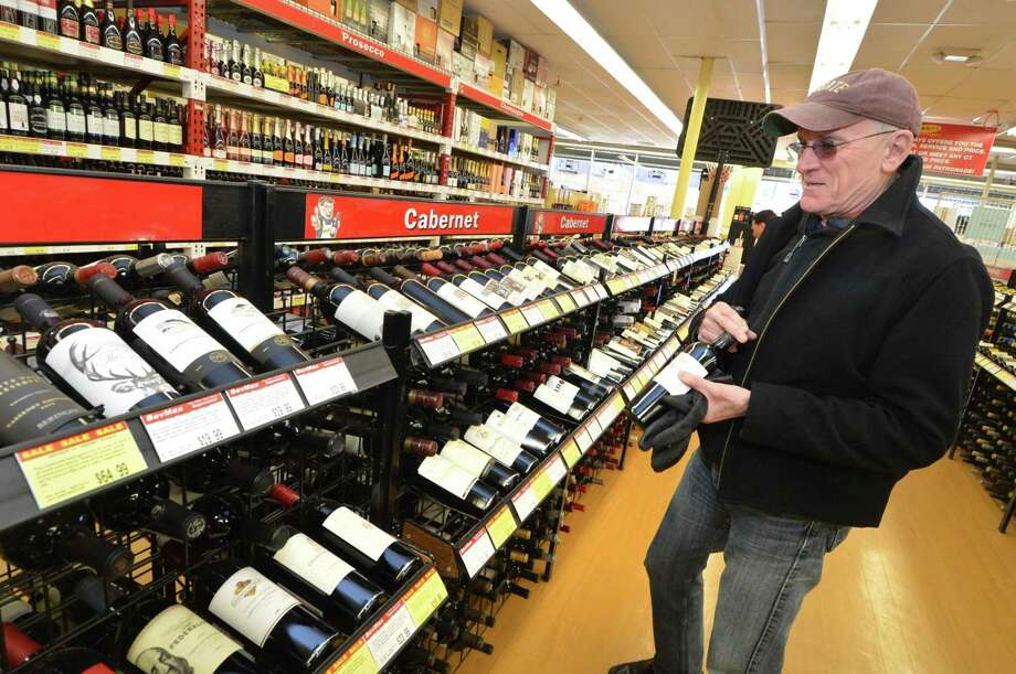 Norwalk's Del Shortliffe buys a few bottles of Cabernet Sauvignon at BevMax on Westport Avenue in 2017. Photo: Alex Von Kleydorff / Hearst Connecticut Media / Norwalk Hour