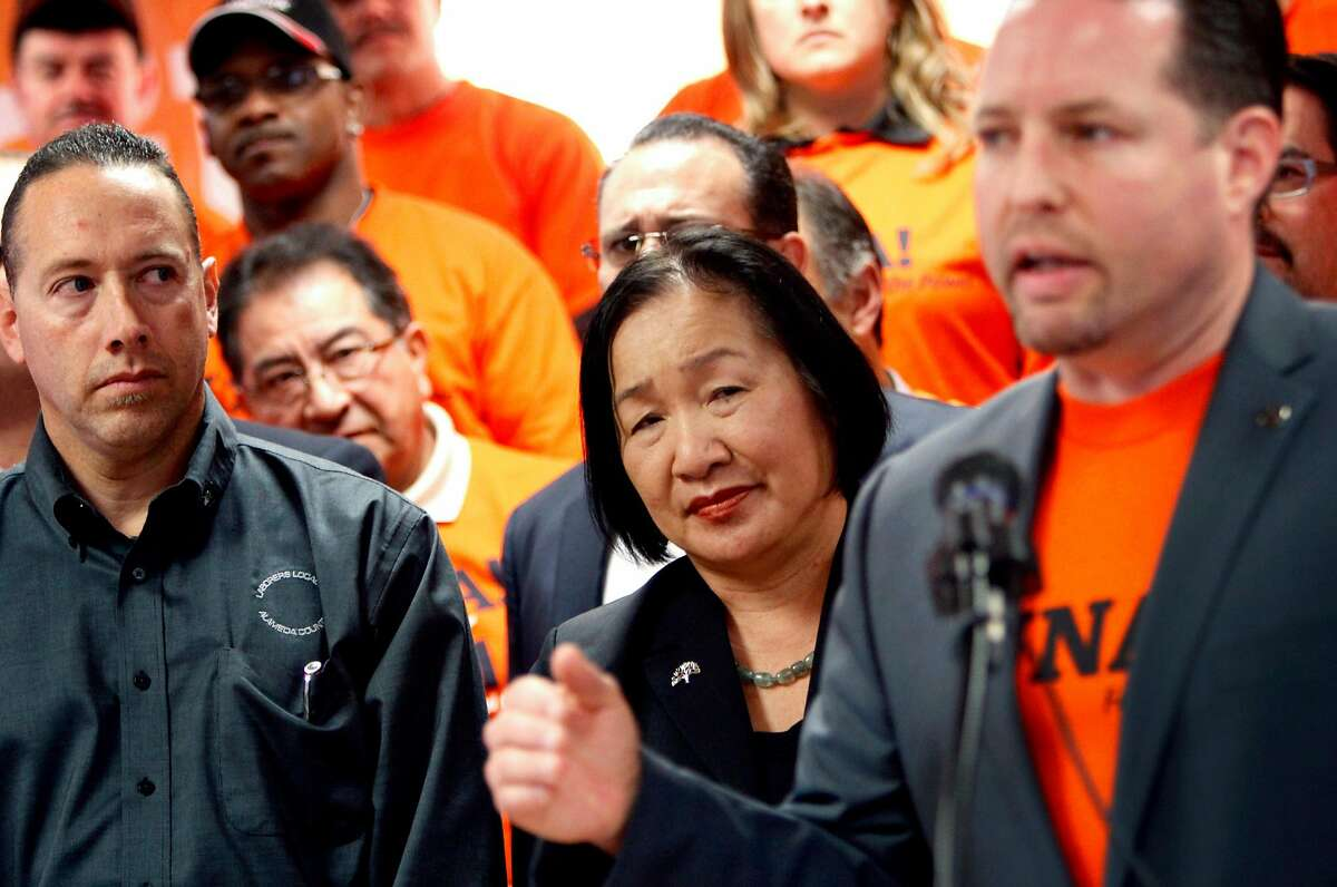 Mayor Jean Quan listens as Vince Courtney speaks during a rally against the recall at the Laborer's Local 304 in Oakland, Calif., Friday, January 13, 2012.