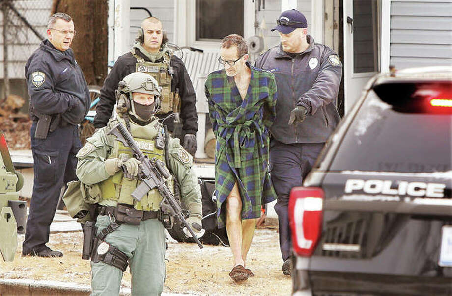 Wood River Police Chief Brad Wells, left, watches as officers escort James A. Corby, 55, in his bath robe and house slippers to a waiting police car early Thursday morning following his arrest in the first block of Eckhard Avenue in Wood River. Members of the ILEAS tactical team raided the house shortly after 8 a.m. to execute a drug-related search warrant. Corby was charged with four felony counts related to unlawful delivery of methamphetamine. A female at the address was also taken into custody but was not expected to be charged, Wells said.