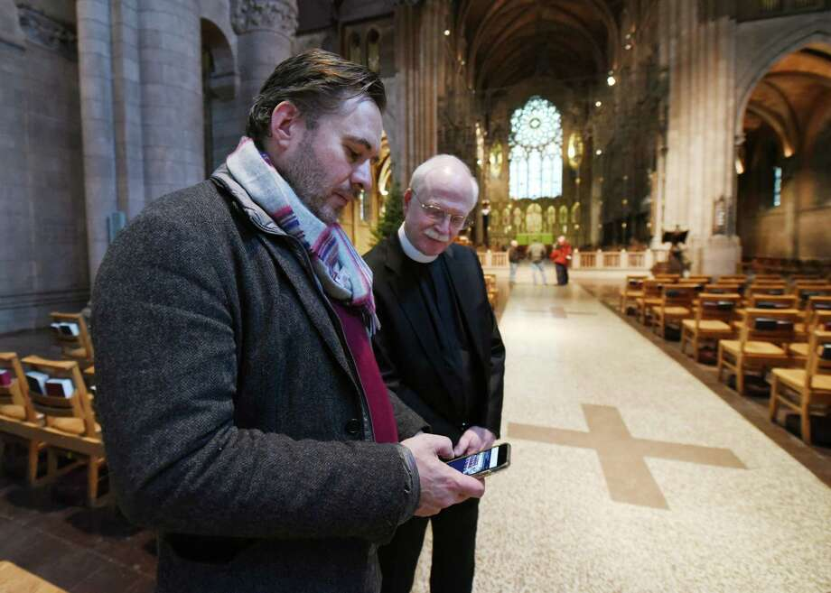 Owen Bush shows The Very Reverend Dr. Leander S. Harding his previous works on Wednesday, Jan. 23, 2019 at The Cathedral of All Saints in Albany, N.Y. (Phoebe Sheehan/Times Union) Photo: Phoebe Sheehan, Albany Times Union / 40045987A