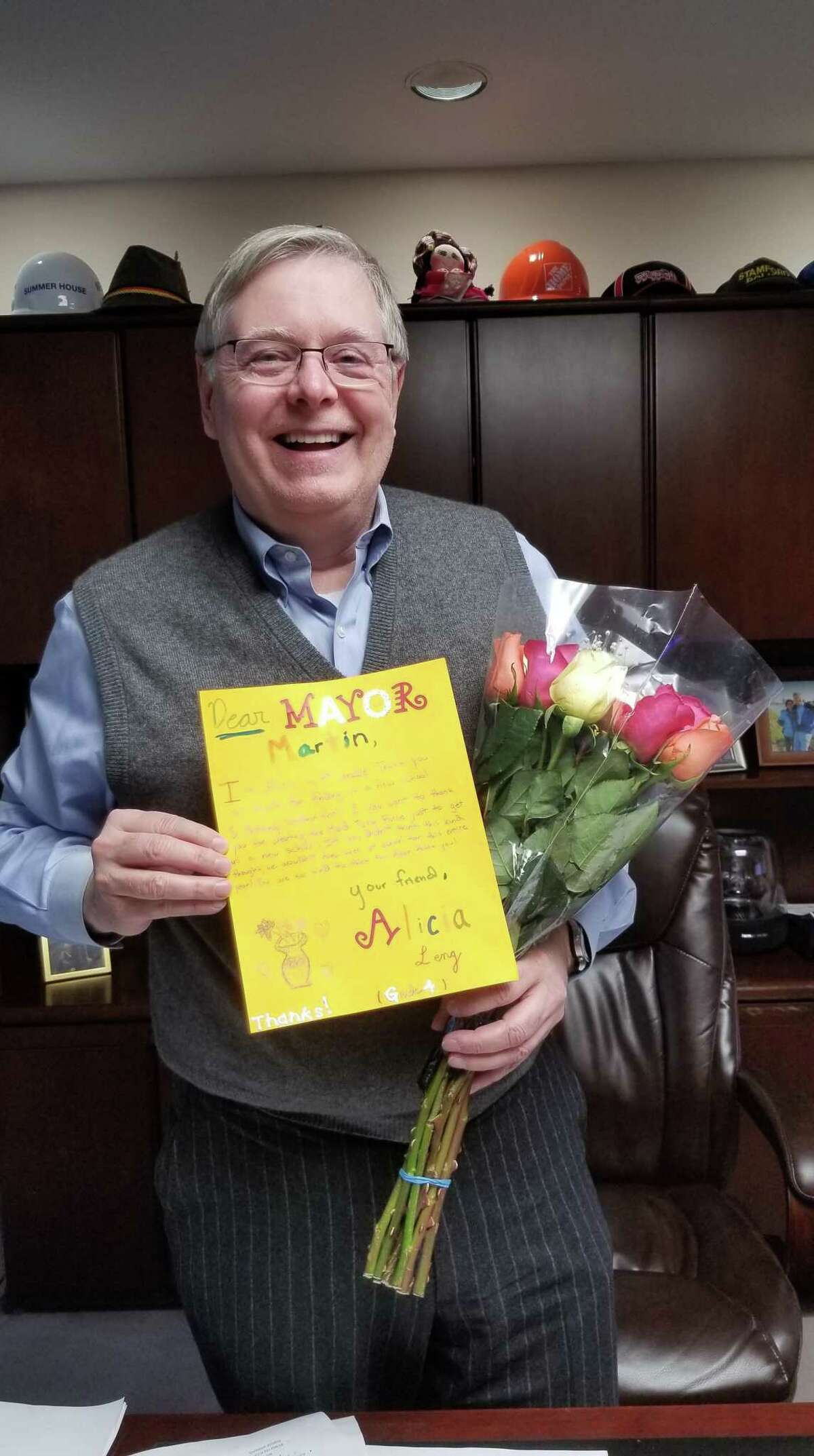 Mayor David Martin of Stamford, Conn. poses with a thank you note and tokens of appreciation from Westover Magnet Elementary School students. Westover students thanked public officials at a Board of Education meeting on Jan. 29, 2019 for moving their school after their old building was closed due to mold.