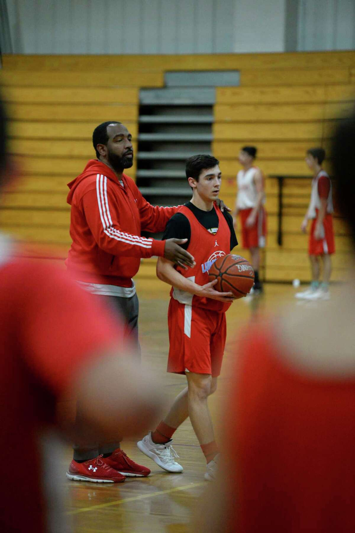 Lumberton's assistance coach Tigee Rideaux helps player Reid Kirk during the team's practice in their gym on Thursday. Photo taken on Thursday, 01/31/19. Ryan Welch/The Enterprise