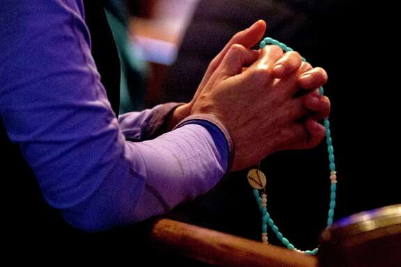 A woman holds a rosary at St. Anthony of Padua Catholic Church, Thursday, Jan 31, 2019, in The Woodlands. The Archdiocese of Galveston-Houston released names of more than 40 priests, clergy and staff 'credibly' accused of sexual abuse or misconduct with a minor since 1950.