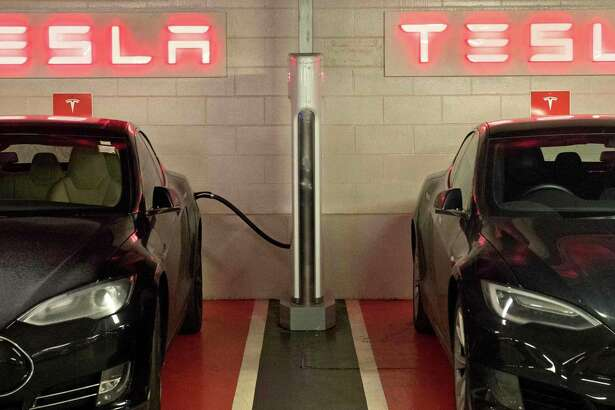(FILES) In this file photo taken on December 19, 2017, Tesla electric cars are charged at a Tesla Supercharger station, in Westfields shopping centre in west London. - Elon Musk's electric car manufacturer Tesla announced on January 18, 2019, it is cutting its workforce by about seven percent as it works to meet its timetable for producing the Model 3. (Photo by Justin TALLIS / AFP)JUSTIN TALLIS/AFP/Getty Images