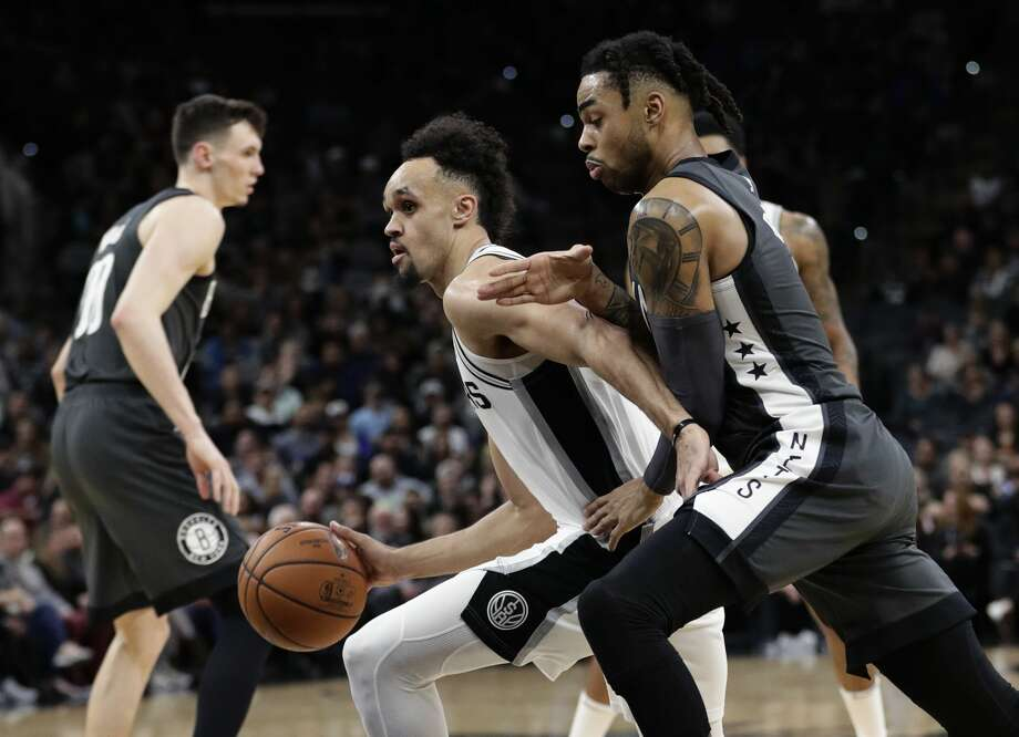 San Antonio Spurs guard Derrick White, center, drives around Brooklyn Nets guard D'Angelo Russell, right, during the first half of an NBA basketball game in San Antonio, Thursday, Jan. 31, 2019. (AP Photo/Eric Gay) Photo: Eric Gay/Associated Press