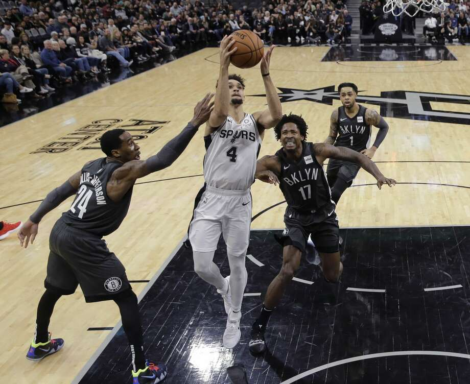 San Antonio Spurs guard Derrick White (4) drives to the basket between Brooklyn Nets forward Rondae Hollis-Jefferson (24) and forward Ed Davis (17) during the first half of an NBA basketball game in San Antonio, Thursday, Jan. 31, 2019. (AP Photo/Eric Gay) Photo: Eric Gay/Associated Press