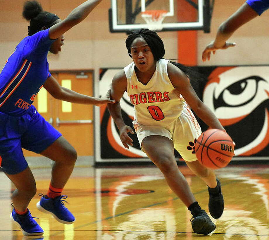 Edwardsville point guard Quierra Love drives to the basket past two East St. Louis defenders during the third quarter Thursday inside Lucco-Jackson Gymnasium.