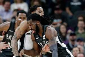 Brooklyn Nets forward DeMarre Carroll (9) drives around San Antonio Spurs guard DeMar DeRozan (10) during the first half of an NBA basketball game in San Antonio, Thursday, Jan. 31, 2019. (AP Photo/Eric Gay)