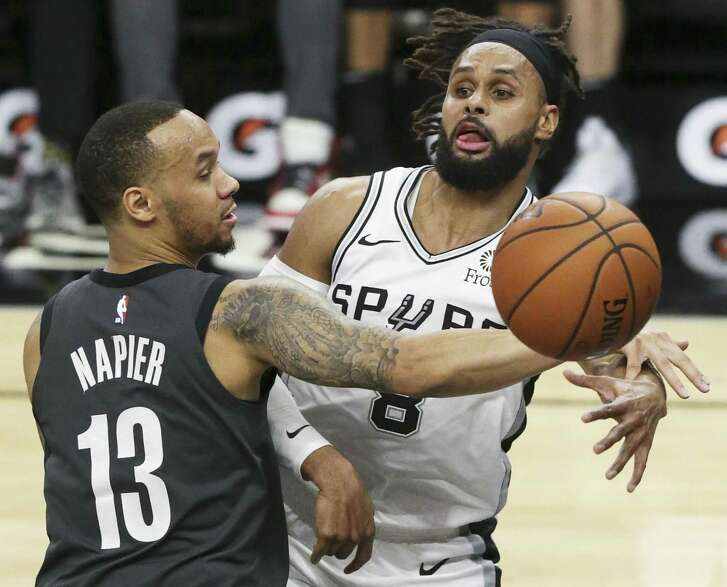 Patty Mills dishes to the side after being covered by Shabazz Napier in the middle as the Spurs host the Nets at the AT&T Center on January 31, 2019.