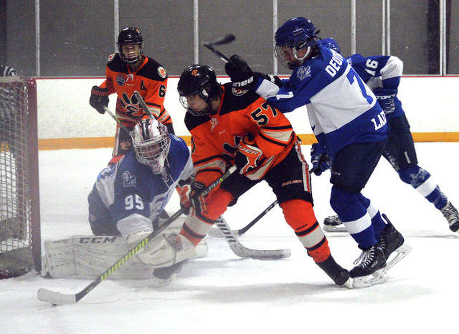 Edwardsville's Justin Harper, middle, tries to put the puck past Ladue goalie Mac Beatrice during the third period of Thursday's game at the East Alton Ice Arena. Photo: Scott Marion/Intelligencer