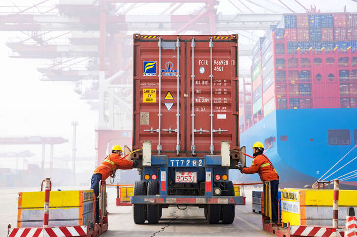 Workers prepare a container at the port in Qingdao, China's eastern Shandong province, on January 14, 2019. - China's global trade volume rose last year but its surplus fell again as its imports outpaced its exports, official data released on January 14 showed amid a bruising trade war with the United States. (Photo by STR / AFP) / China OUT (Photo credit should read STR/AFP/Getty Images)