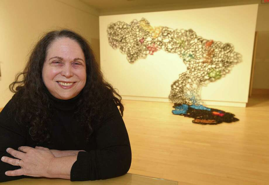 "Artist Suzan Shutan of Hamden is photographed in front of her piece titled ""Drift,"" a site specific installation made of tar paper, lotka paper and industrial glue. The piece is part of the ""Fluid Terrain"" exhibit at the Greenwich Library's Flinn Gallery. She will lead an artist's talk at 2 p.m. Sundayat the Flinn Gallery on the exhibit, which features the work of three female artists whose inspiration virtually flows from nature. For more info, visit flinngallery.com. Photo: Matthew Brown / Hearst Connecticut Media / Stamford Advocate"