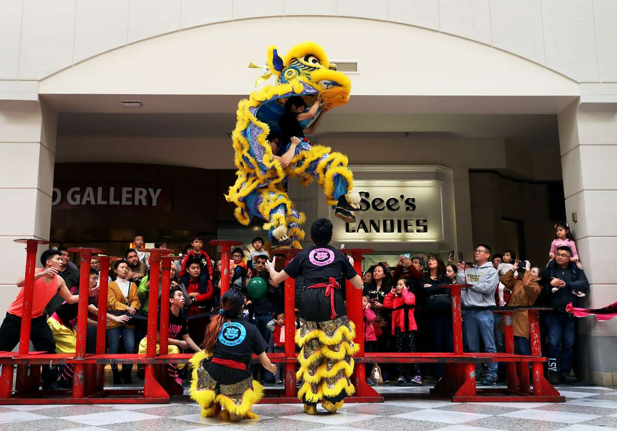 Norman Lau (far left), director of LionDanceME, watches as Jacky Li (center left), 16, and Brandon Wong (center right), 17, leap during their performance at Macy's Center Court at Hillsdale Mall in San Mateo, Calif., on Saturday, January 26, 2019.