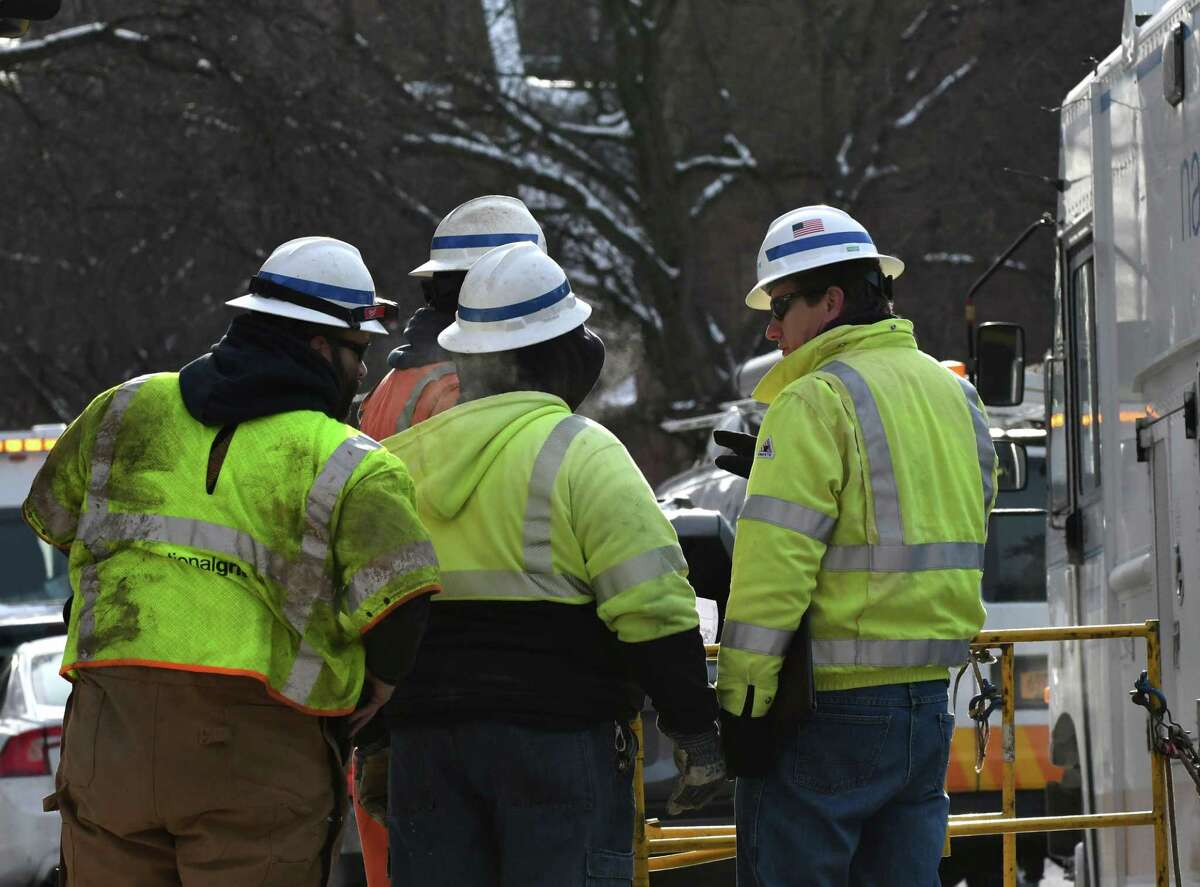 Crews from National Grid work to repair lines on State Street and Henry Johnson Blvd. where concussion and debris from a utility explosion caused damage to nearby buildings and vehicles on Friday, Feb. 1, 2019, in Albany, N.Y. (Will Waldron/Times Union)