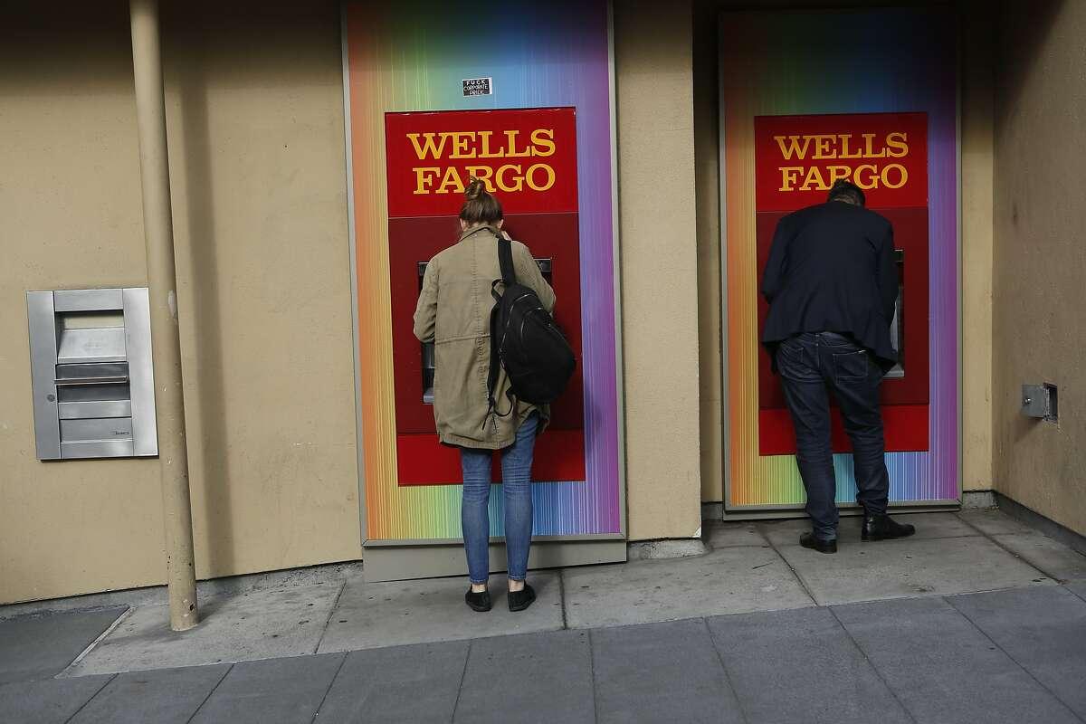 Caroline Nattinger, center, and Brian Rush use Wells Fargo ATMs on Castro Street on Tuesday, June 19, 2018 in San Francisco, Calif.