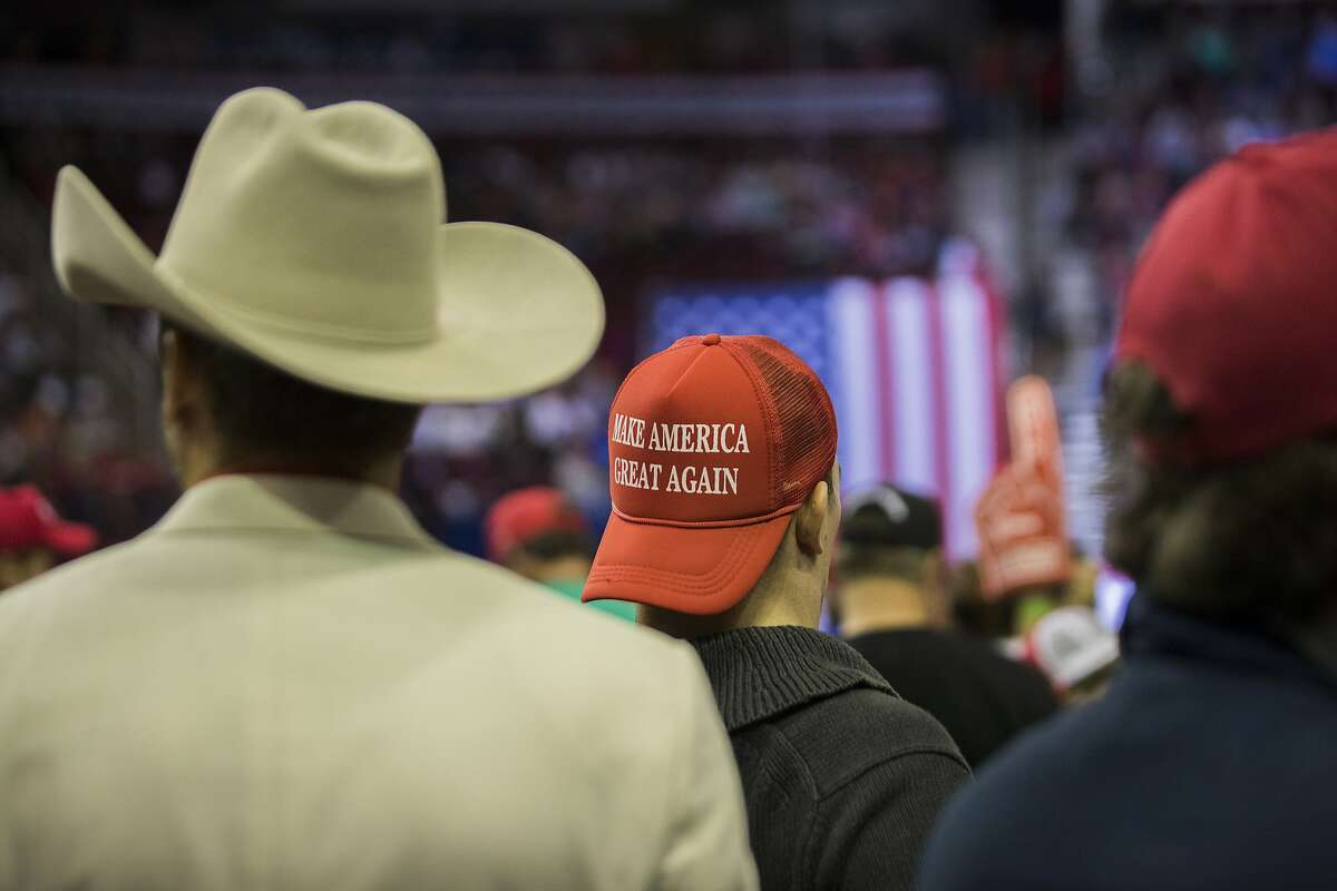 MAGA hat and a cowboy hat worn by President Donald Trip supporters at a rally in Houston, Monday, Oct. 22, 2018.