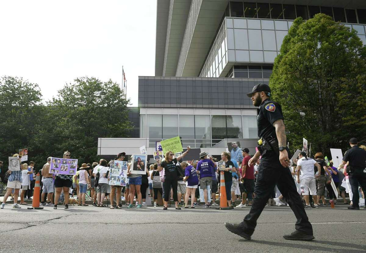 Protesters demonstrate outside the Purdue Pharma headquarters at 201 Tresser Blvd., in downtown Stamford, Conn., on Aug. 17, 2018.