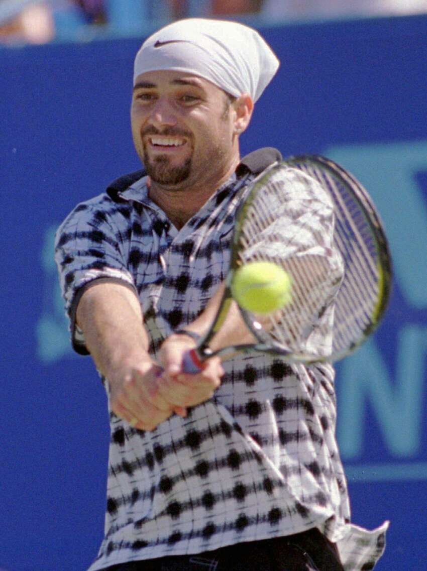 Andre Agassi of Las Vegas, Nev., returns a backhand shot to Richard Krajicek of the Netherlands during their championship round singles match at the Volvo International tennis tournament in New Haven, Conn., Sunday, Aug. 20, 1995. Agassi won the match and the title by defeating Krajicek 3-6, 7-6 (7-2), 6-3. (AP Photo/Bob Child)