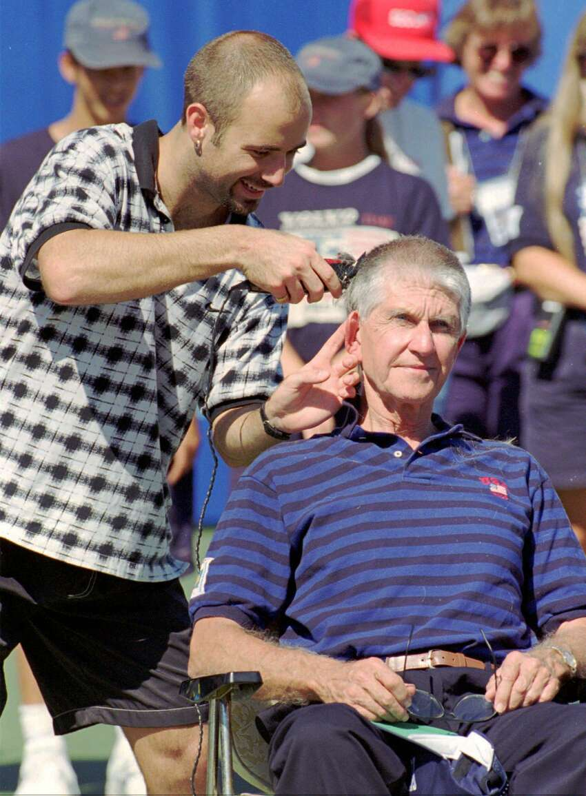 Andre Agassi, left, shaves Volvo International Tennis Tournament Director Jim Westhall's head after Agassi won the Volvo International singles title in New Haven, Conn., Sunday, Aug. 20, 1995, by defeating Richard Krajicek of the Netherlands 3-6, 7-6(7-2), 6-3. Agassi made a bet with Westhall that if he won the tournament Westhall, who is known for having a large head of hair, would let him shave Westhall's head. (AP Photo/John Dunn)