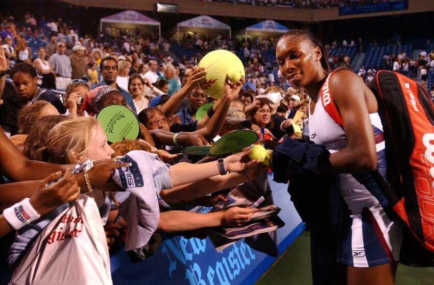 Venus Williams signs autographs after defeating Meghann Shaughnessy on Aug. 20, 2002