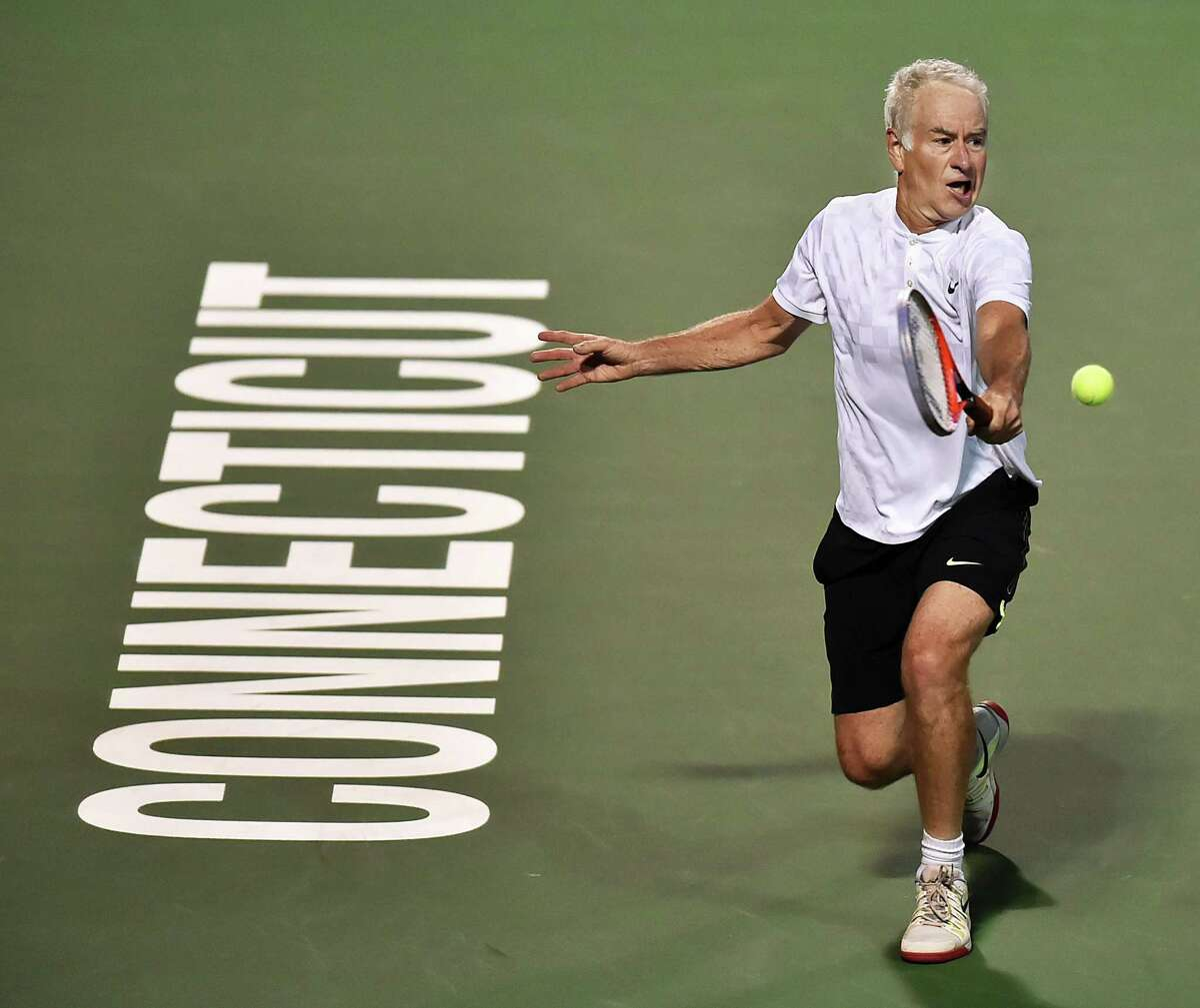 John McEnroe backhands a return to James Blake on Stadium Court Friday, August 24, 2018 in an Invesco Series QQQ Men's Legend championship match at the Connecticut Open at the Connecticut Tennis Center at Yale in New Haven. Blake won, 6-4.