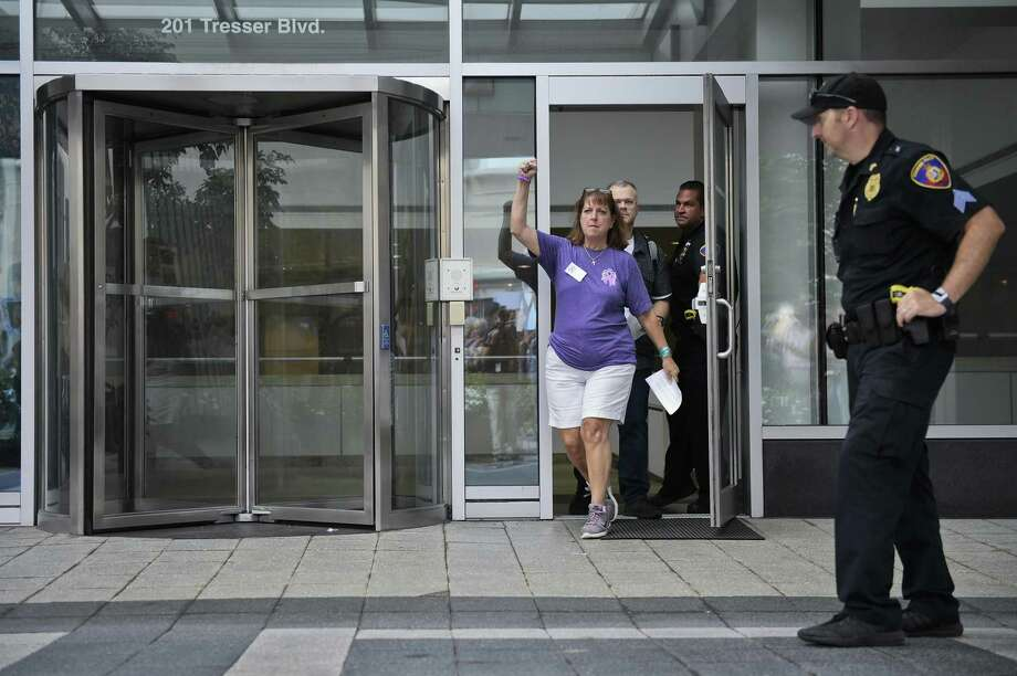Cheryl Juaire pumps her fist in the air after delivering a letter intended for Purdue Pharma CEO Craig Landau, at the company's headquarters in Stamford, Conn., on Friday, Aug. 17, 2018. Juaire organized a protest by family and friends who have lost loved ones to OxyContin and opioid overdoses. (AP Photo/Jessica Hill) Photo: Jessica Hill / Associated Press / Copyright 2018 The Associated Press. All rights reserved