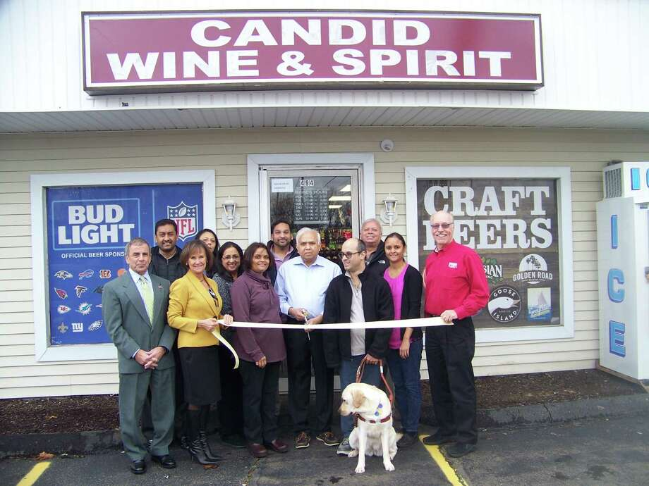 CHEERS!: Candid Wine & Spirit, 494 Washington Ave. in North Haven, recently celebrated its grand opening with a ribbon-cutting ceremony. From left are North Haven First Selectman Mike Freda; Dee Prior-Nesti, executive Director, Quinnipiac Chamber of Commerce; Bhavna Patel, owner; Navin Patel, owner; Vishal Patel with guide dog Febe; Unnati Patel, Kevin O'Rourke of Fish Window Cleaning, past board chairman of the Quinnipiac Chamber of Commerce; and (back row, center) Jay Patel. The package store offers a variety of top shelf scotch, bourbon, tequila and vodka in addition to a large wine list and craft beer. For information, call 203- 239-3562. Photo: Contributed Photo