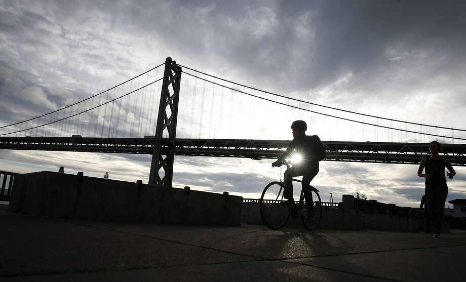 Bicyclists and joggers head up The Embarcadero in San Francisco. Photo: Paul Chinn / The Chronicle