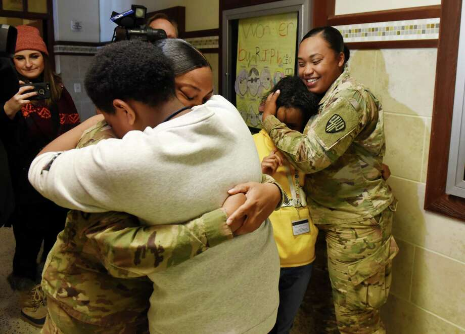 Christopher Sang, left, and Breannie Jackson, right, are reunited with their mothers, Erica Gonzalez, left, and Jessica Gonzalez, right, during a reunion at Hackett Middle School on Friday, Feb. 1, 2019, in Albany, N.Y. The two soldiers, who are also sisters, have been away on military deployment since March of last year. (Will Waldron/Times Union) Photo: Will Waldron, Albany Times Union / 40046100A