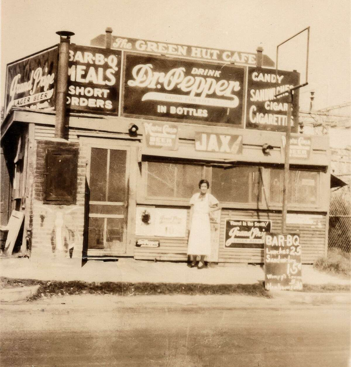 Leona Ginn stands near a vertical brick smoker on the front of The Green Hut Café on Quitman Street in 1934.