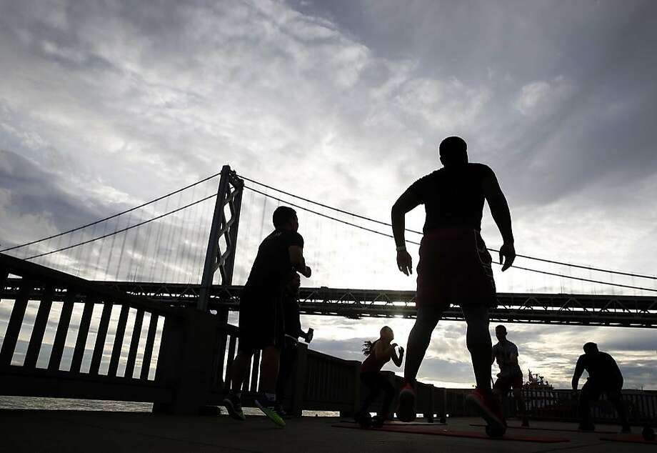 A fitness group exercises below clouds gathering in the sky above The Embacadero in San Francisco, Calif. on Friday, Feb. 1, 2019 before a rainstorm. Photo: Paul Chinn, The Chronicle