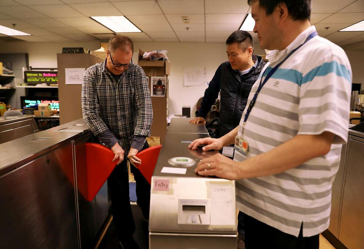 Jim Allison (left), media relations manager, tries to open a barrier as John Yen, manager for fare collection engineering, and Weldon Chen, senior computer systems engineer, look on in the Fare Collection Engineering Machinery Laboratory at BART headquarters in Oakland, Calif., on Tuesday, January 29, 2019. BART is testing new, sturdier fare gates meant to ward off fare cheaters.