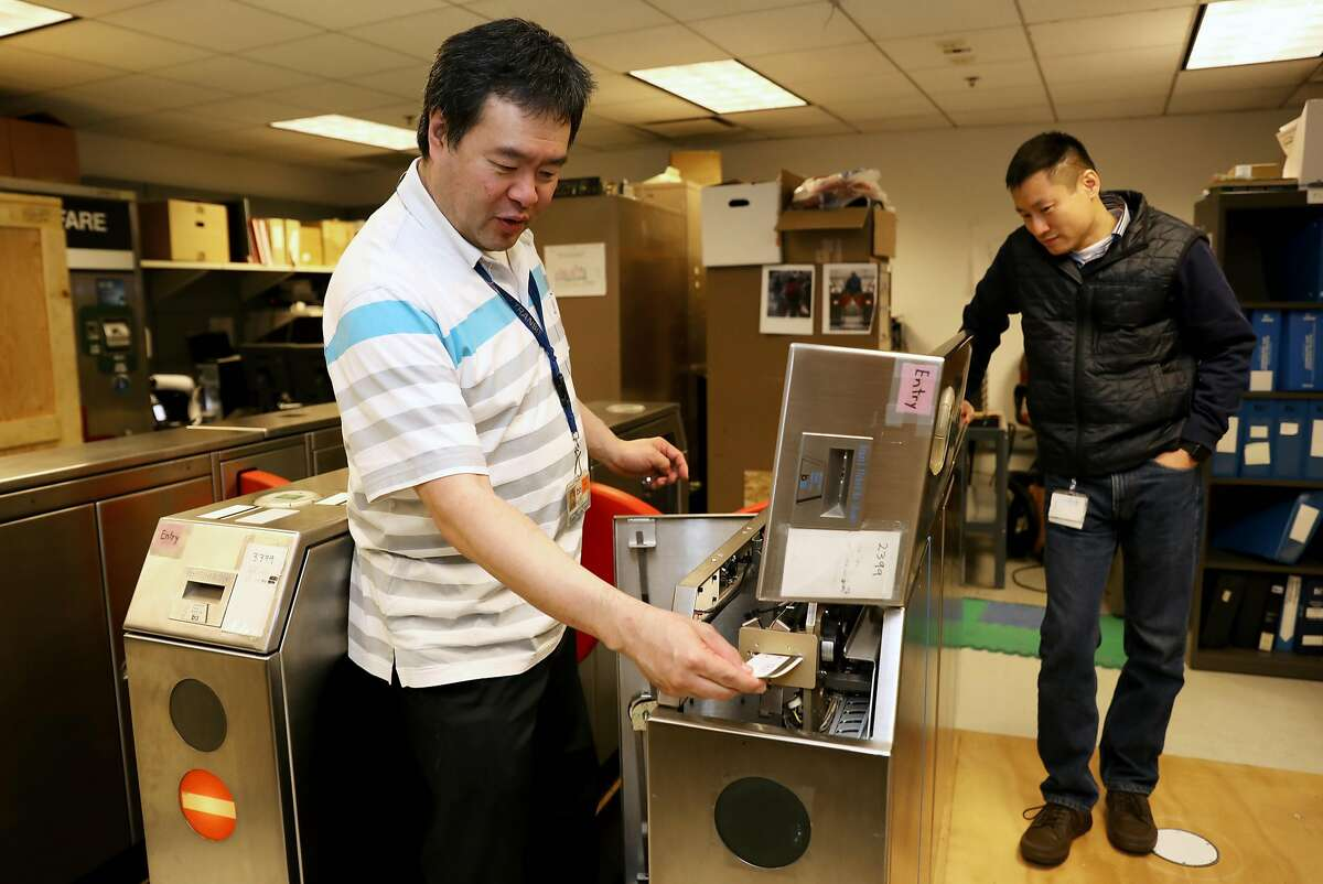 Weldon Chen (left), senior computer systems engineer, inserts a test paper card into a fare gate as John Yen, manager for fare collection engineering, looks on in the Fare Collection Engineering Machinery Laboratory at BART headquarters in Oakland, Calif., on Tuesday, January 29, 2019. BART is testing new, sturdier fare gates meant to ward off fare cheaters.
