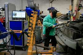 Tom Lehman, senior technician, uses a resistance spot welder while installing an upper frame rail to a car while working at George V. Arth & Son auto body repair shop on Monday, November 20, 2017 in Oakland, Calif.