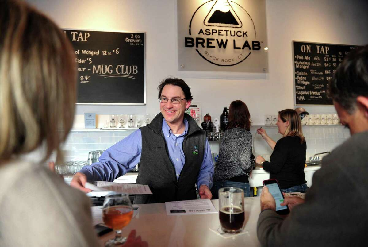 Aspetuck Brew Lab owner Peter Cowles chats with customers at the micro brewery on Fairfield Avenue in Bridgeport, Conn., .