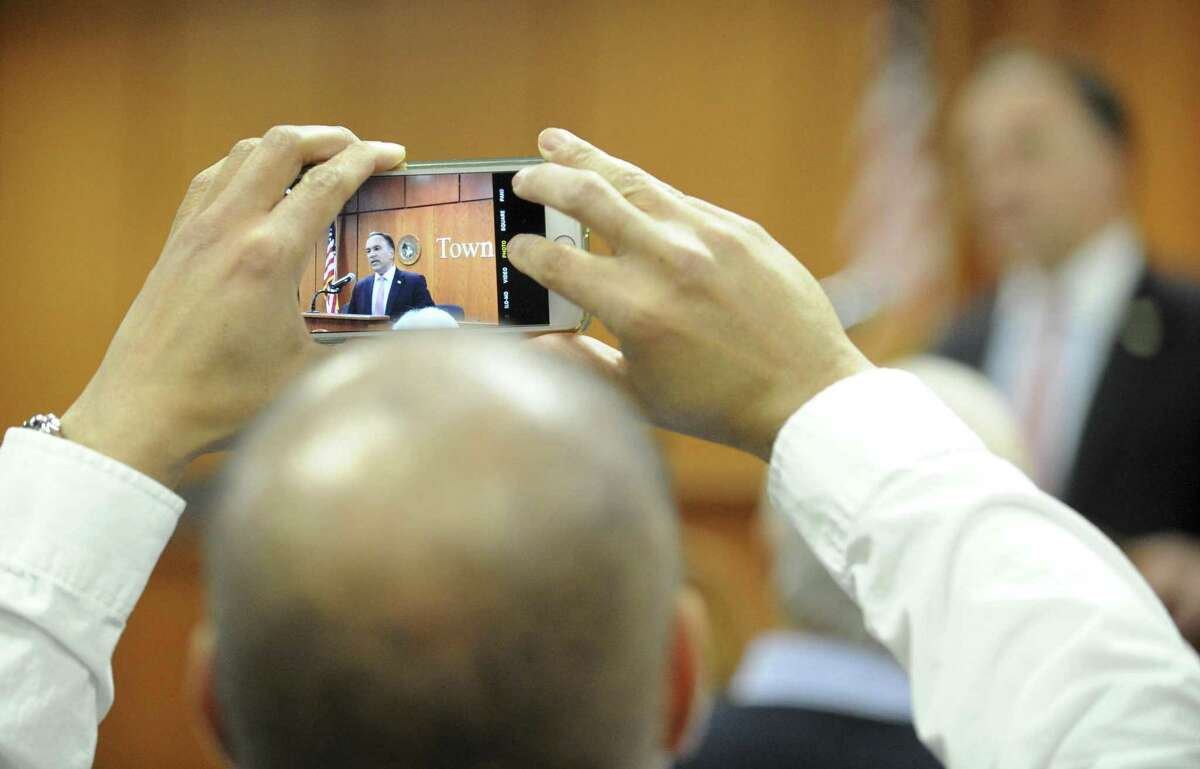 A reporter snaps a photo as First Selectman Peter Tesei announces he will not seek reelection before a crowd of supporters gathered in the meeting room at the Greenwich Town Hall on Friday, Feb. 1, 2019 in Greenwich, Connecticut.