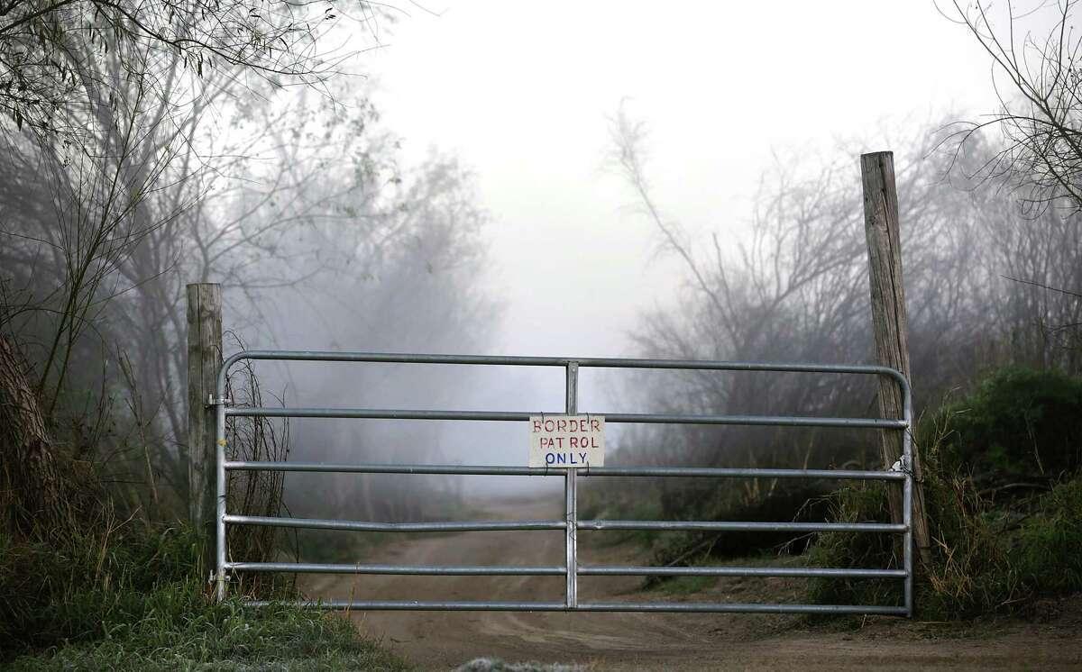 A gate to a ranch road is seen in the early morning fog along the Rio Grande near San Ygnacio.