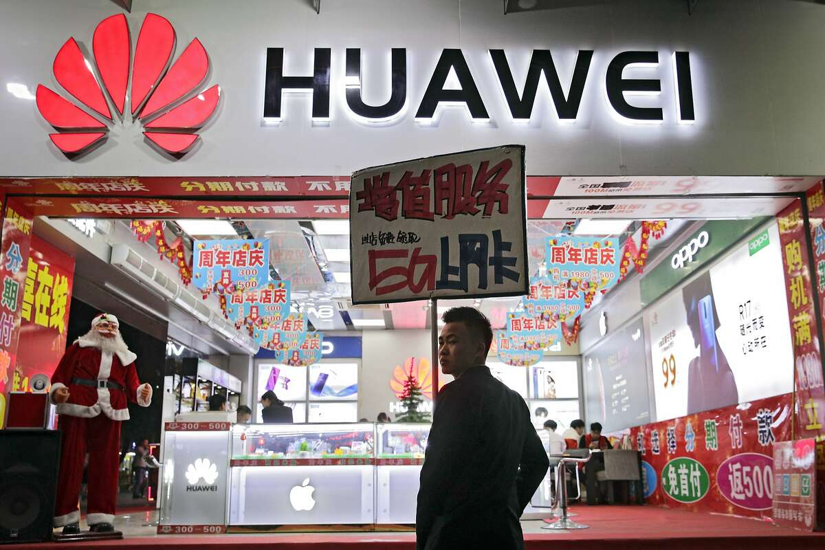 FILE - In this Dec. 18, 2018, file photo, a worker holds a sign promoting a sale for Huawei 5G internet services at a mobile phone retail shop in Shenzhen in south China's Guangdong province. China has called on the United States to 'stop the unreasonable crackdown' on Huawei following the tech giant's indictment on charges of stealing technology, violating trade sanctions and lying to banks. (AP Photo/Andy Wong, File)