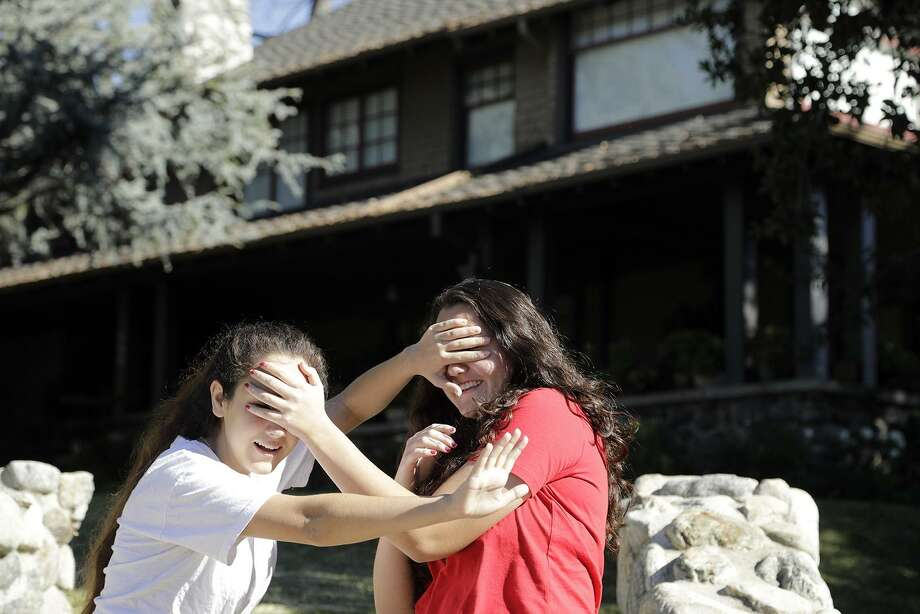 """Abby Olague, 15, left, and her sister Bella Olague, 14, of Chino, Calif. improvise their """"Bird Box"""" pose on Jan. 4 at the """"Bird Box"""" house in Monrovia, Calif. A reader advises those who are curious to know what it is really like to be blind to view the """"My Heart is Not Blind"""" exhibit at the Witte Museum. Photo: Myung J. Chun /TNS / Los Angeles Times"""
