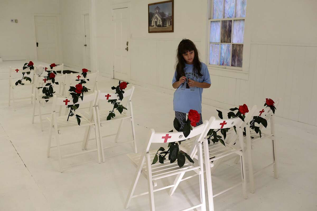 Haley Ward, 8, looks at the chairs dedicated to her family members during a memorial held a year after the shooting.