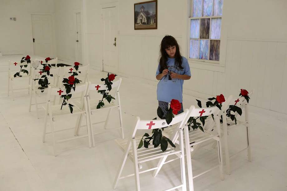 Haley Ward, 8, looks at the chairs dedicated to her family members during a memorial held a year after the shooting. Photo: Lisa Krantz /Staff File Photo / Lisa Krantz/San Antonio Express-News