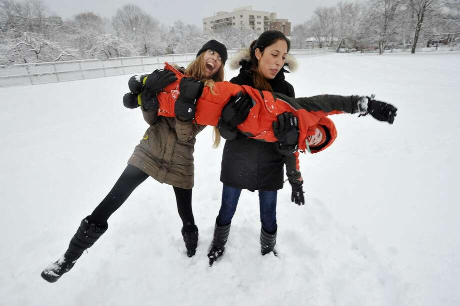 Caretakers Monserrat Jifkins, left, and her sister, Giovanna, play with Eric Cooper in the snow at Scalzi Park in Stamford on Feb. 3, 2014. Photo: Jason Rearick / Jason Rearick / Stamford Advocate