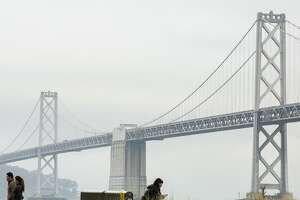 The Bay Bridge as people walk along the Embarcadero during a cloudy morning following overnight rain on Thursday, Jan. 31, 2019, in San Francisco, Calif.