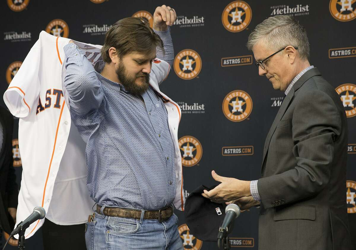 The Houston Astros new pitcher Wade Miley puts on the Astros jersey that he received from general manager Jeff Luhnow during a press conference at Minute Maid Park on Friday, Feb. 1, 2019, in Houston. Miley and the Astros reached a one-year, $4.5 million deal.
